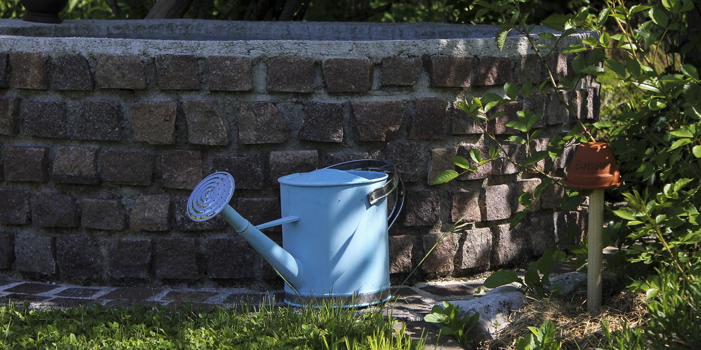 Gießkanne vor Brunnen